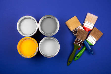 Four open cans of yellow and gray paint with brushes on blue background. Top view.