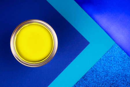 Brush on open can of yellow paint on blue background. Color of the year in interior. Color of the year in interior. Changing colors of the year concept. 免版税图像