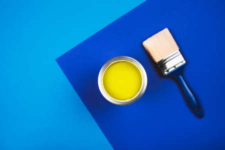 Brush and open can of yellow paint on blue background. Color of the year in interior. Changing colors of the year concept.