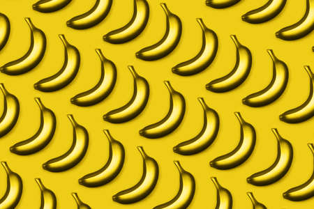 Yellow bananas on monochrome background. Flat lay style. Trendy photo ispired by color of the year 2021
