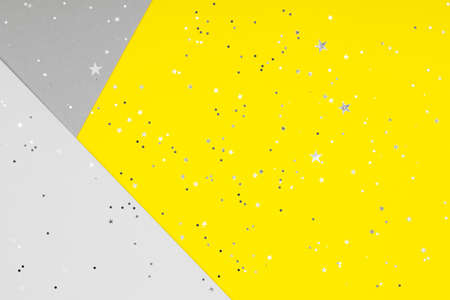 Paper background with metallic shiny stars and glitter in two trendy colors - yellow and gray. Demonstrating colors of 2021 year.