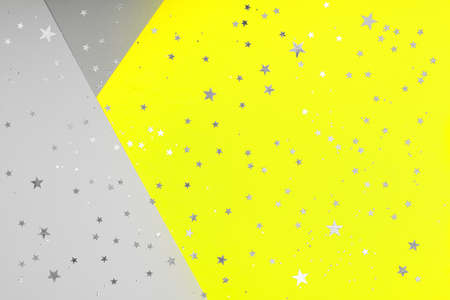 Paper background with metallic shiny stars and glitter in two trendy colors - yellow and gray. Demonstrating colors of 2021 year. Festive backdrop for your design.