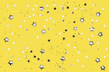 Yellow background with shiny silver glitter on it. Dots, stars and little sparkles in flat lay stile. Festive concept.