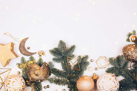 Christmas decorations on white background. Fir tree, golden toys, sparkles and lights. Place for your text 免版税图像