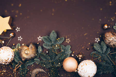 Christmas decorations on dark background. Fir tree, golden toys, sparkles and lights. Place for your text