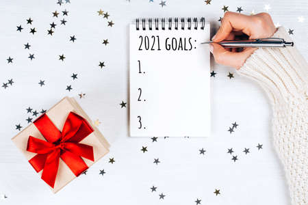 Holiday decorations and notebook withnew year resolutions list on white rustic table, flat lay style. Planning concept for 2021