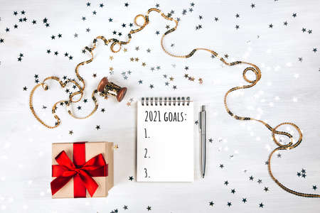 Holiday decorations and notebook with new year resolutions list on white rustic table, flat lay style. Planning concept for 2021