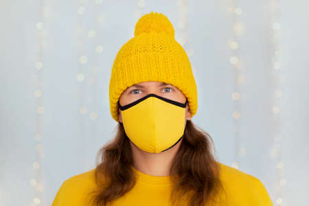 Man in yellow knitted hat and fabric mask looking at camera against fairy lights on winter day