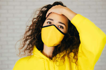 Female in bright yellow mask and hoodie touching curly hair and looking at camera during pandemic