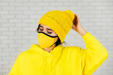 Female in bright yellow hoodie and mask adjusting knitted hat against gray brick wall 免版税图像