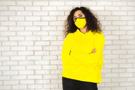 Female in bright yellow mask and hoodie with curly hair looking at camera during pandemic 免版税图像