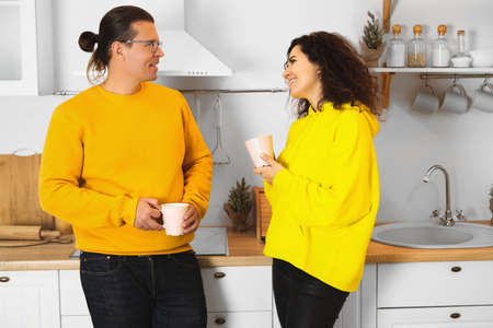 Cheerful man and woman in similar clothes smiling and looking at each other while enjoying hot beverages in cozy kitchen at home