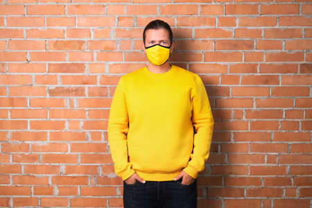Adult male in yellow sweatshirt and mask holding hands in pockets and looking at camera while leaning on brick wall during pandemic