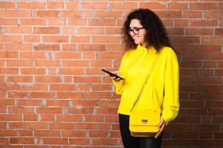Happy young female in yellow hoodie and glasses smiling and browsing smartphone against brick wall 免版税图像