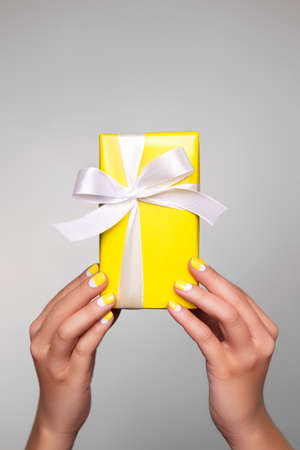 Demonstrating trendy colors of year 2021 - Gray and Yellow. Colorful gift with white ribbon in womans hands