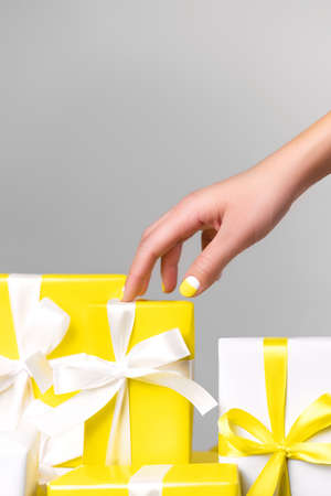 Demonstrating trendy colors of year 2021 - Gray and Yellow. Yellow gift with white ribbon