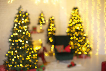 Defocused  of illuminated room with coniferous trees and fireplace decorated for Christmas celebration at home