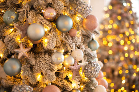 Close up branches of white coniferous tree decorated with glittering balls and shiny light garland on Christmas day
