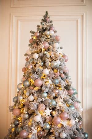White coniferous tree decorated with glittering balls and shiny light garland on Christmas day
