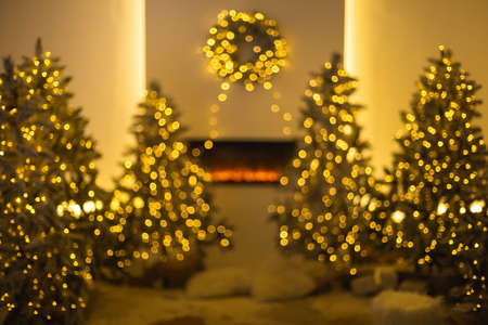 Defocused of illuminated Christmas trees placed near fireplace with traditional wreath in evening in cozy room at home 免版税图像