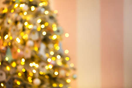 Defocused  of coniferous tree with light garlands placed near pink wall in cozy room during Christmas celebration at home