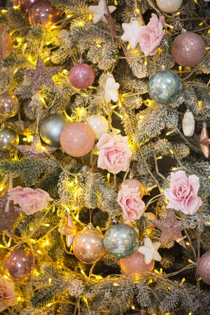 Illuminated coniferous tree decorated with various baubles and flowers in Christmas evening at home