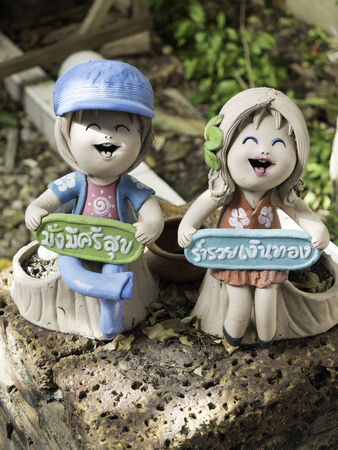 Happy boy and girl doll pottery with 2 Thai word   Boy   Have a healthy rich, Girl   be rich  photo