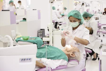 Rama dental hospital, Bangkok, Thailand - Feb 27, 2013   Dentist woking on and old patient in Rama Hospital