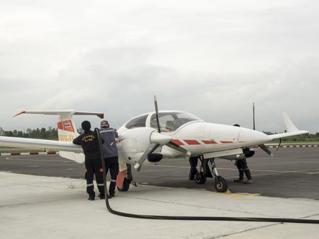 Bangkok, Thailand - Aug 5, 2014 : Filling up aircraft by two man