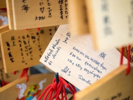 happieness: Kyoto, Japan - June 28, 2014 :  Horse wooden prayer tablets at Kiyomizu dera Kyoto (The Horse year) with thai hade writing. Pray for happieness good life healthy peace luck by write praying word in wooden. Editorial