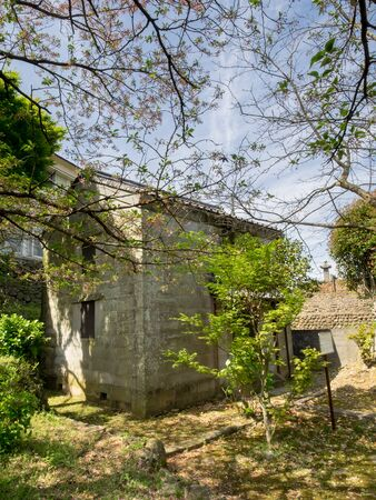 warehouse building: NAGASAKI JAPAN  Apr 7 2015 :  Stone warehouse at takashima shuhans former residence.Two story wall stone with pan tile gabled roof. This building use for store gunpowder.Buildings made of stone are quite rare therefore has great historical value.