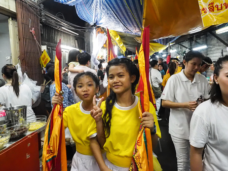 lad: Bangkok, Thailand - October 20, 2015 : Two littel girl in yellow shirt hold flag and do V-post in parade of vegetarian festival at ta lad noi