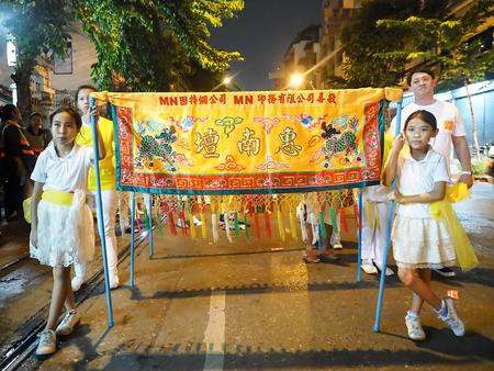 worshipper: Bangkok, Thailand - October 20, 2015 : Girls Parade hold china banner prepare to walk on charearn kung road in vegetarian festival
