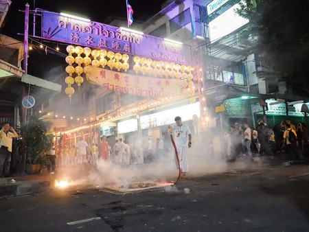 lad: Bangkok, Thailand - October 20, 2015 : Man in white suit hold a firecracker in hand and swing in front of Saan Jao Joe Sue Gong entrance for celebrate god in vegetarian festival at ta lad noi.