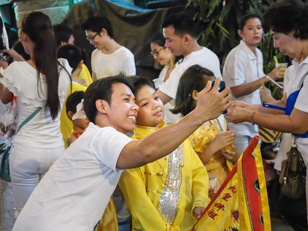 lad: Bangkok, Thailand - October  20, 2015 : unidentifies two men Selfie by smart phone in vegetarian festival at ta lad noi area Editorial