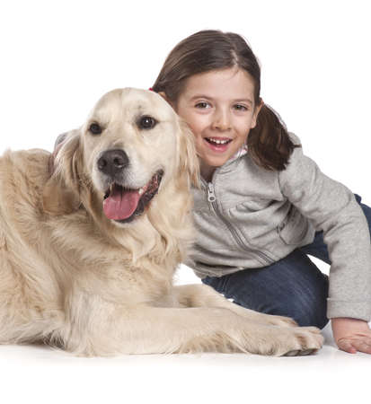 pet therapy: Little girl playing with her dog golden retriever