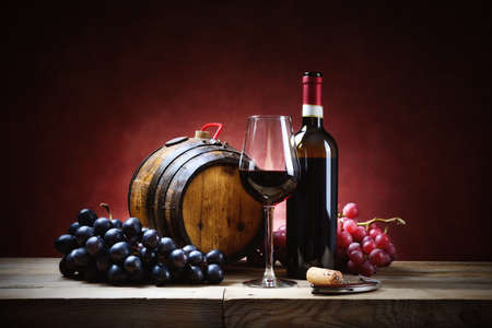 Red wine glass with bunches of grapes, bottle and small barrel on old wooden table.