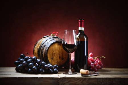 Verre à vin rouge avec grappes de raisin, bouteille et petit tonneau sur une vieille table en bois.