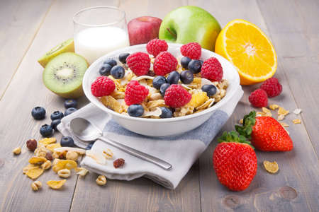Breakfast with muesli and fruit on wooden rustic table.