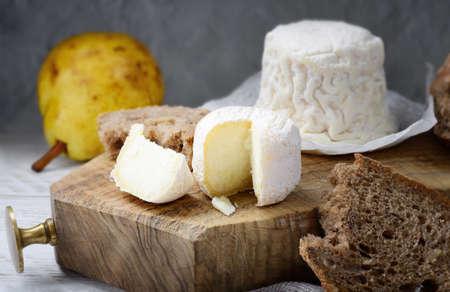 Crottin de Chavignol and Chabichou du Poitou, French goat cheeses in rustic setting. Progressive focus.