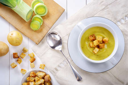 Leek and potato soup with croutons on white wooden table, top view.