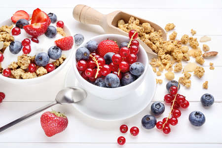 Breakfast with crunchy muesli and berries on white wood background.