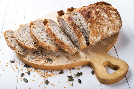 Organic seed bread. Sourdough bread. Bread cut in slices on a white wood background.