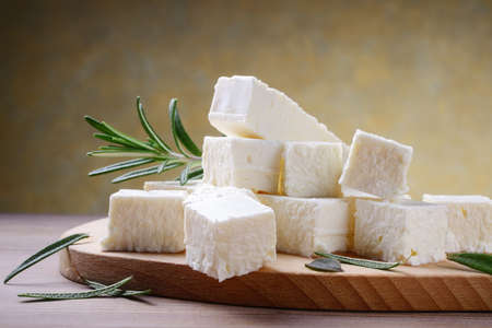 Feta cheese with rosemary on cutting board.