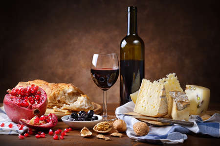 Red wine, cheese, walnuts, olives, pomegranate and bread in rustic setting.