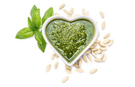Genoese pesto sauce with basil and pine nuts isolated on white background, top view.