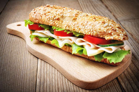 Sandwich with ham, cheese, lettuce, cucumber and tomato.