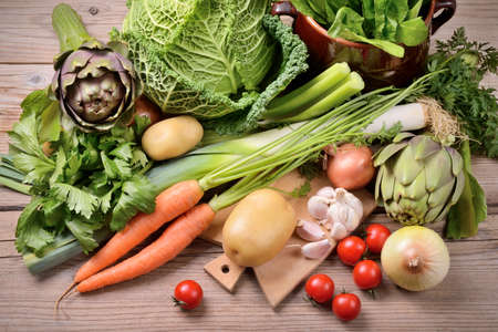 Assorted fresh vegetables with chopping board on wooden table, top view. Stok Fotoğraf
