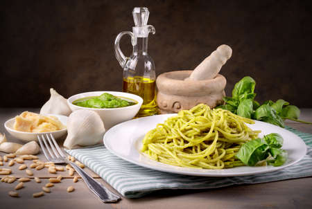 Spaghetti with genoese pesto sauce in rustic setting.