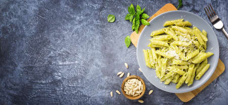 Penne pasta with basil pesto, genoese pesto. Top view, space for text. Archivio Fotografico